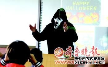 一名外教老师戴着面具给学生讲解万圣节的故事。